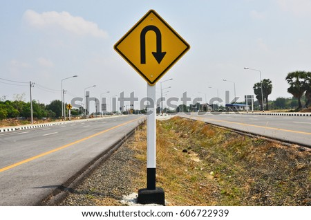 U turn ahead sign in the middle of two roads