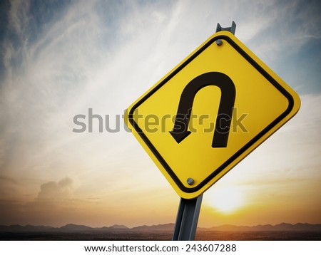U turn road sign on setting sun background
