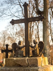 Užupis, Vilnius, Lithuania - Bronze Angels and cross on a tomb on local cemetery in Vilnius, Europe