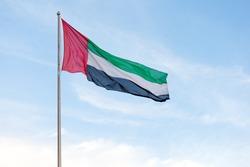 UAE flag waving in the blue bright sky, national symbol of UAE