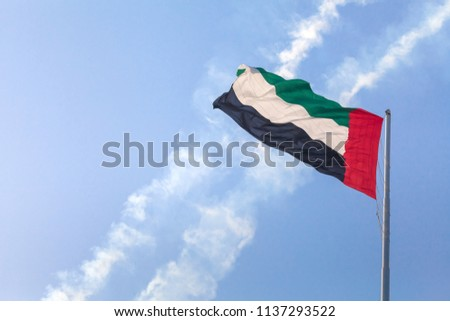 UAE flag waving in the sky, national symbol of UAE. UAE flag day.