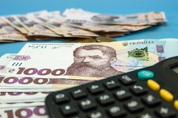 UAH . Money of Ukraine 1000 and 500 hryvnia with a calculator on a blue background. Financial concept.