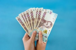 UAH Money of Ukraine 1000 hryvnia in hand, Ukrainian banknote isolated on a blue background