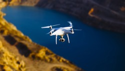 Uav drone copter flying with digital camera above opencast mining quarry.