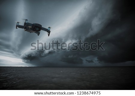UAV drone copter flying with digital camera.Drone with high resolution digital camera. Flying camera take a photo and video.The drone with professional camera takes pictures of the rain storm on sea