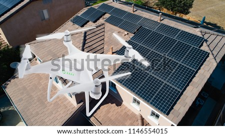 UAV Drone Inspecting Solar Panels On Large House.