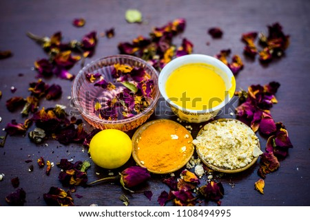 Ubtan or face pack of lemon and gram flour with rose water with some rosa leaves on wooden surface.
