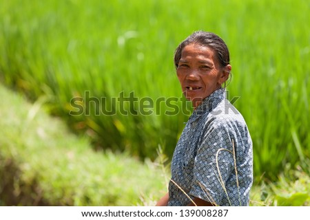 UBUD, BALI - SEP 22: Female worker takes a rest near green rice field at Ubud, Bali, Indonesia on Sep 22, 2012.