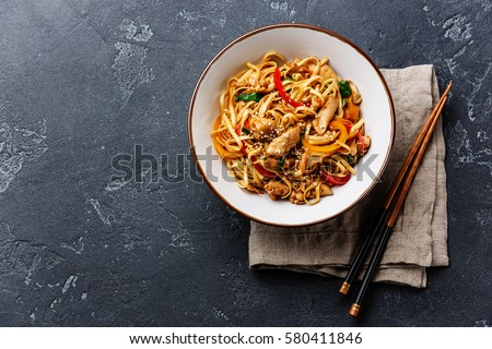 Udon stir-fry noodles with chicken meat and sesame in bowl on dark stone background copy space