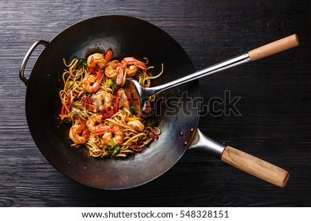 Udon stir-fry noodles with shrimp and vegetables in wok pan on black burned wooden background Zdjęcia stock ©