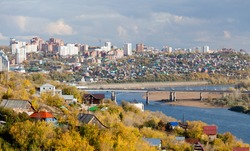 Ufa city at the autumn. You can see Belaya (White) river and modern district behind the bridge.