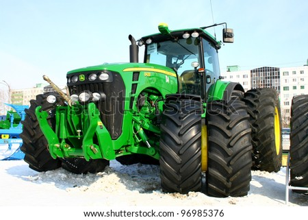 "UFA, RUSSIA - MARCH 14: Large modern John Deere 8430 four wheel drive tractor with double wheels exhibited at the annual motor show ""Agrocomplex"" on March 14, 2011 in Ufa, Russia."