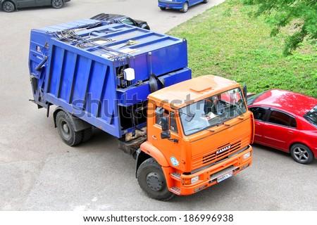 UFA, RUSSIA - MAY 28, 2012: Orange KAMAZ 53605 garbage truck at the city street.