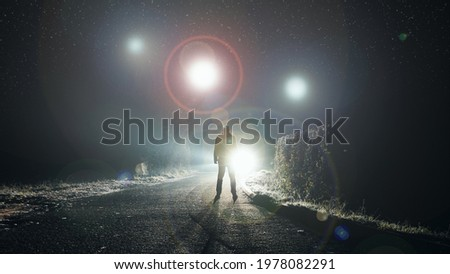 UFO concept. Glowing orbs, floating above a misty road at night. With a silhouetted figure looking at the lights.