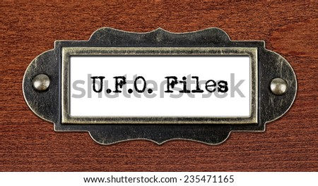 ufo files - file cabinet label, bronze holder against grunge and scratched wood