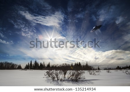 UFO hovering over an Alaskan snow scene with a sunburst and clouds.