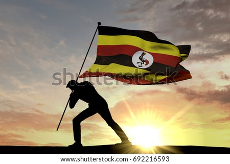 Shutterstock Uganda flag being pushed into the ground by a male silhouette. 3D Rendering