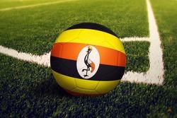 Uganda flag on ball at corner kick position, soccer field background. National football theme on green grass.