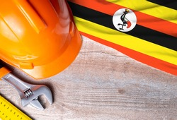Uganda flag with different construction tools on wood background, with copy space for text. Happy Labor day concept.