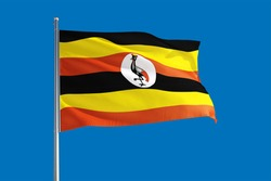 Uganda national flag waving in the wind on a deep blue sky. High quality fabric. International relations concept.