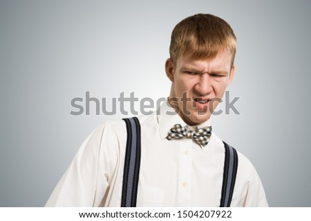 Ugh, how disgusting. Displeased redhead hipster. Emotional boy has dissatisfied facial expression as sees something abominable or detestable. Portrait of guy wears white shirt, bow tie and suspenders