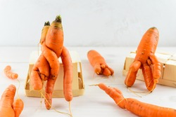 Ugly carrot on a white wooden table. Ugly vegetables concept.