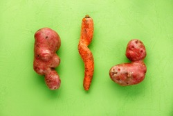 Ugly funny vegetables, lumpy potatoes and a twisted carrot on a green background. Coarse vegetables or food waste concept. Top view, copy space.