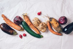 Ugly organic rotten vegetables with mutations on craft paper background. Concept of zero waste production. Copy space. Spoiled non gmo vegetables with dots. Compost