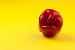 Ugly red bell pepper on yellow background with copy space. Concept - reduction of food organic waste. A deformed crooked vegetable looks like a grimace of a fairytale character.