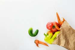 Ugly vegetables in a paper bag. Ugly food concept, flat lay.