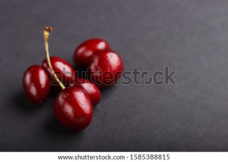 Ugly weird red sweet cherry on black background. side view, close up, copy space, macro, trendy.