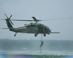 UH-60 Black Hawk. Soldier climbing up ladder on to A UH 60 Black Hawk which is a utility tactical transport helicopter .