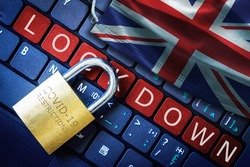 UK COVID-19 coronavirus lockdown restrictions concept illustrated by padlock on laptop red alert keyboard buttons and face mask with British flag.