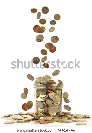 uk currency falling into a savings jar
