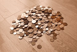 UK currency, hundreds of British copper and silver colored coins randomly piled ontop of each other, one pound coins, fifty pence, twenty pence, two pence, one pence,