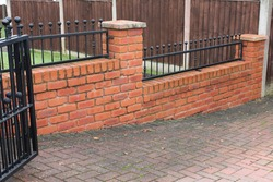 UK domestic brick wall with railings
