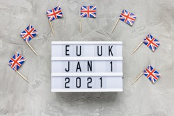UK flags and text EU UK January 1 2021 on gray background. Brexit, trade deal, transition period, changes and new rules concept. Flat lay, copy space