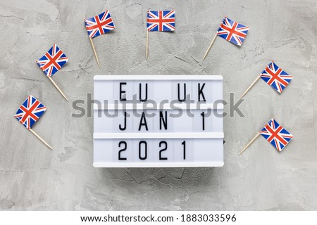 Photo of  UK flags and text EU UK January 1 2021 on gray background. Brexit, trade deal, transition period, changes and new rules concept. Flat lay, copy space