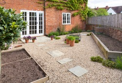 UK garden in spring with empty vegetable beds. Courtyard style Victorian garden with gravel and York stone paving