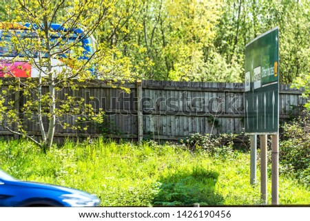 uk motorway directional sign with car and bus in front of it. #1426190456