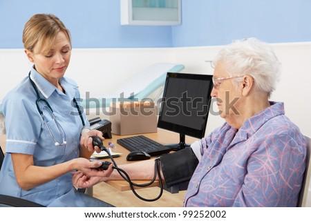 UK nurse taking senior woman's blood pressure - stock photo