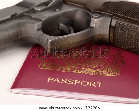 UK passports and a handgun on white background - stock photo