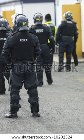 Uk police officers in full riot gear at the scene of a public disturbance.