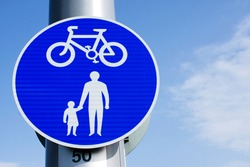 UK Road sign cycle and pedestrian pathway against a blue cloudy sky
