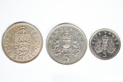 UK Shilling, 5 New Pence and 5 Pence coins showing the process of coin development through the adoption of decimal currency within the UK
