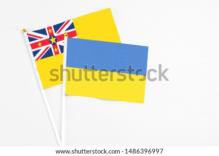 Ukraine and Niue stick flags on white background. High quality fabric, miniature national flag. Peaceful global concept.White floor for copy space. #1486396997