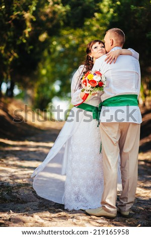 Ukraine. Happy ukrainian wedding (bridal) couple in the ukrainian style. Beautiful bride and groom in the ukrainian style are standing with bouquet. Female and male models.