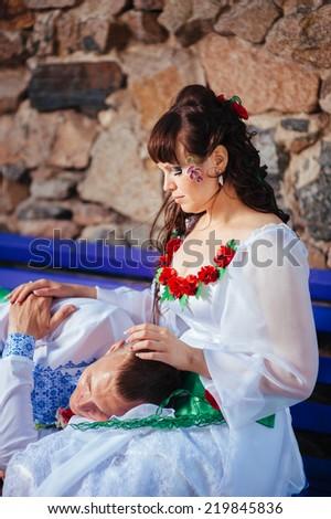 Ukraine. Happy ukrainian wedding (bridal) couple in the ukrainian style. Beautiful bride and groom in the ukrainian style are standing with bouquet. Female and male models.  park summer outdoor