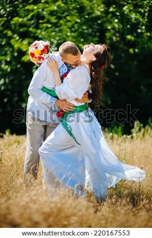 Ukraine. Happy ukrainian wedding (bridal) couple in the ukrainian style. Beautiful bride and groom in the ukrainian style are standing with bouquet. Female and male models. . park summer outdoor