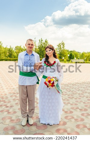 Ukraine. Happy ukrainian wedding (bridal) couple in the ukrainian style. Beautiful bride and groom in the ukrainian style are standing with bouquet. Female and male models. Indoors, close up.